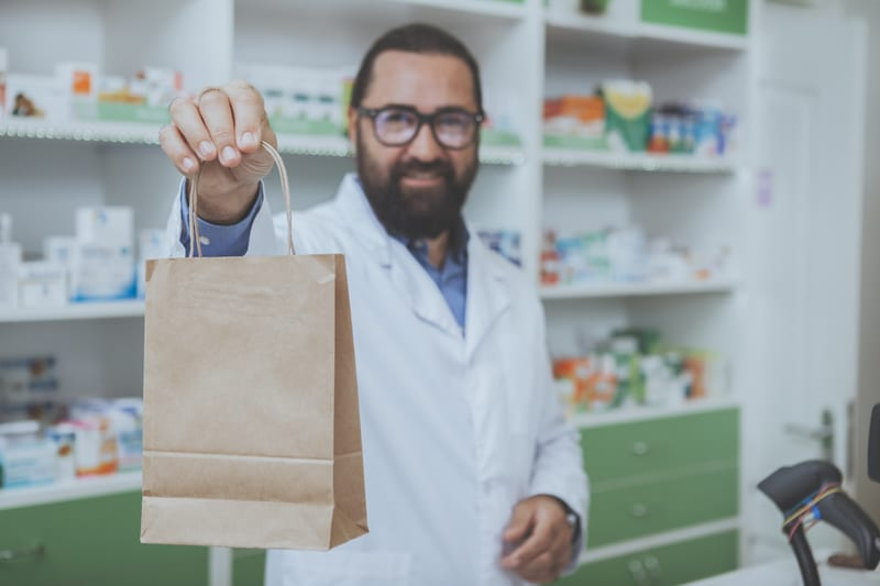 Pharmacist with bag of painkillers for knee pain