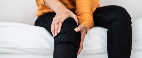 woman-knee-pain-on-sofa