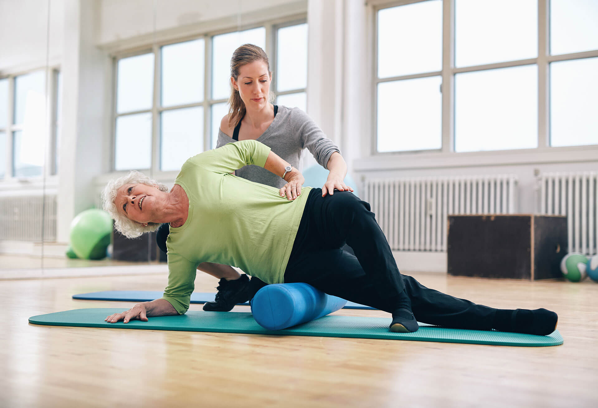 Physical therapist helping woman use foam roller